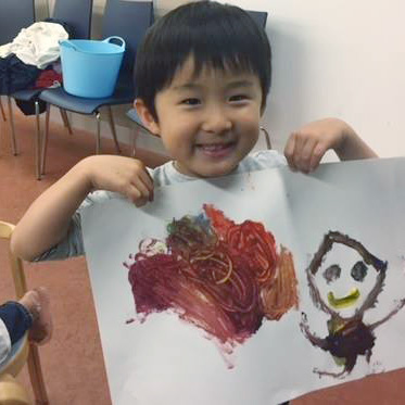 photo of young child holding up finger painting